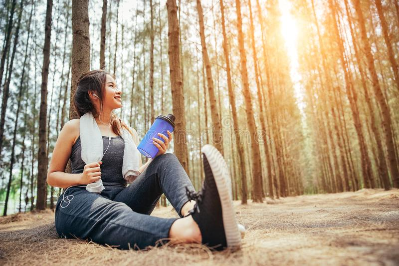 Asian girl is exercising, nd drinking cool water and listening music stock images
