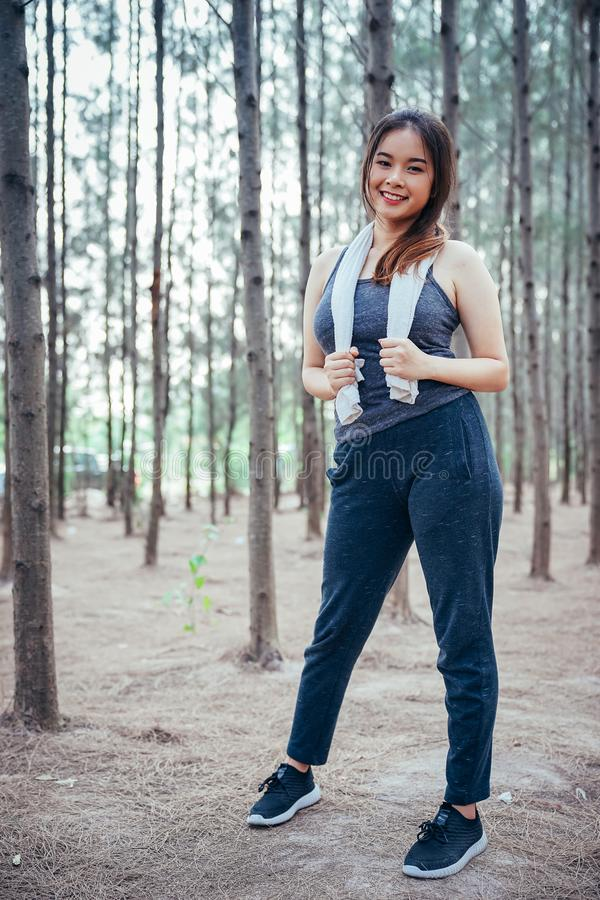 Asian girl is exercising at the weekend in a pine forest stock photography