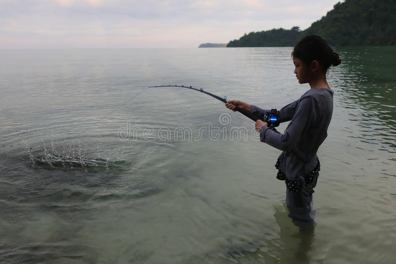 Asian girl fishing with rod and reel in the sea stock photos