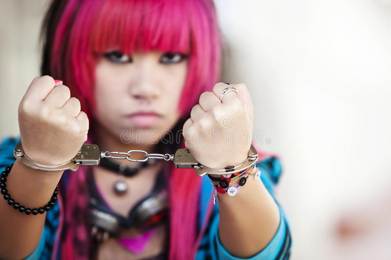 Asian girl with handcuffs. Young asian girl showing handcuffs on her wrists stock photo