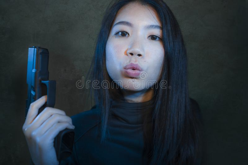 Asian girl with handgun - dramatic portrait of young attractive and dangerous looking Korean woman holding gun posing playful dark royalty free stock photography
