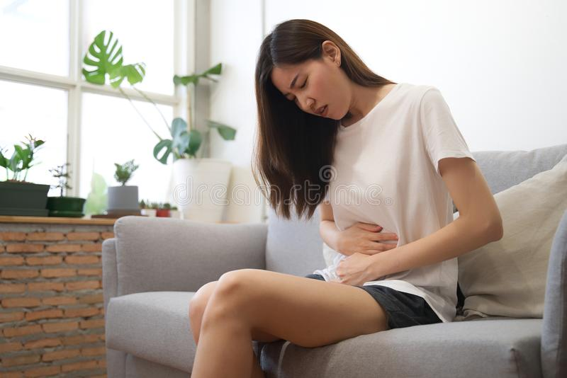 Asian girl having period is sitting on sofa and feeling much of painful on her stomach with unknown reason. She holds onto her royalty free stock photography