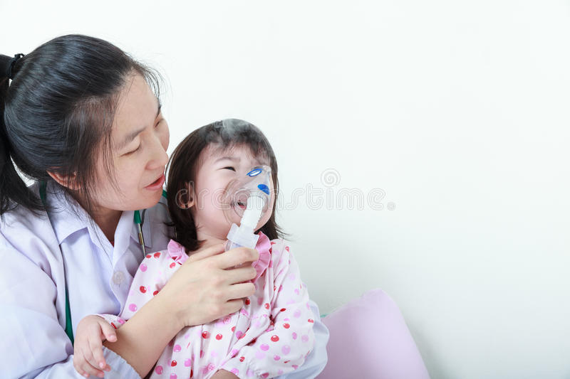 Asian girl having respiratory illness helped by health professional with inhaler. royalty free stock photos