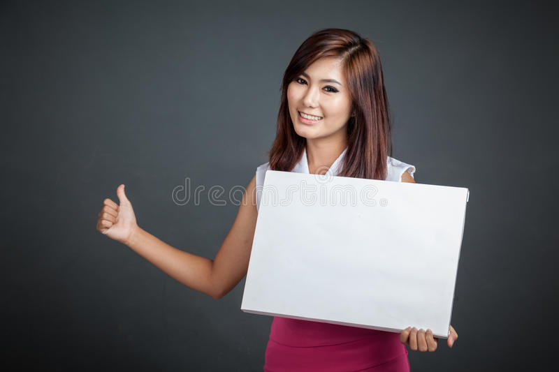 Asian girl hold a blank sign and hitchhiking. On gray background royalty free stock photo
