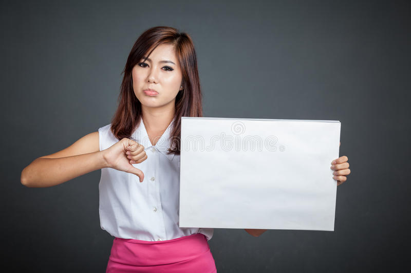 Asian girl hold blank sign and show thumbs down. On gray background royalty free stock photo