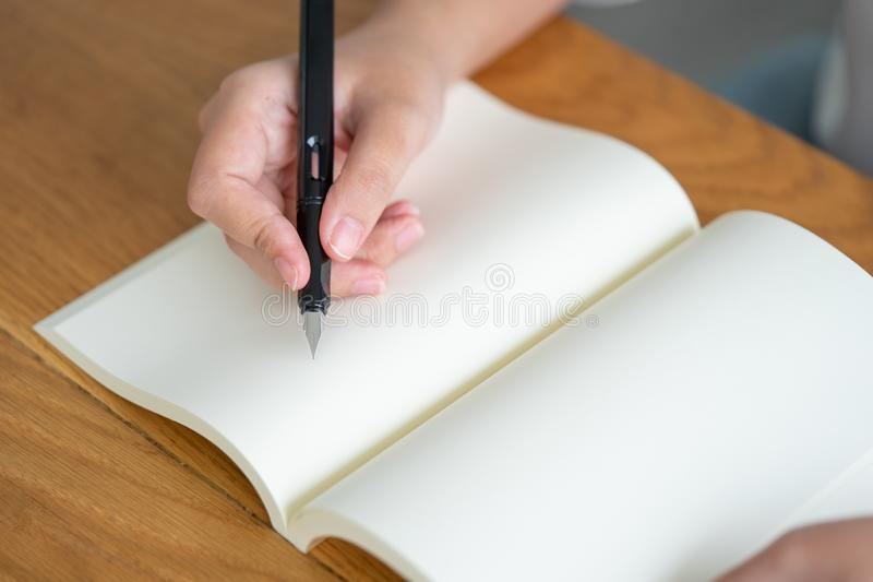 Asian girl holding a black pen writing into an empty book. Diary writing stories recorded impressive. Memories on a wooden table stock photography