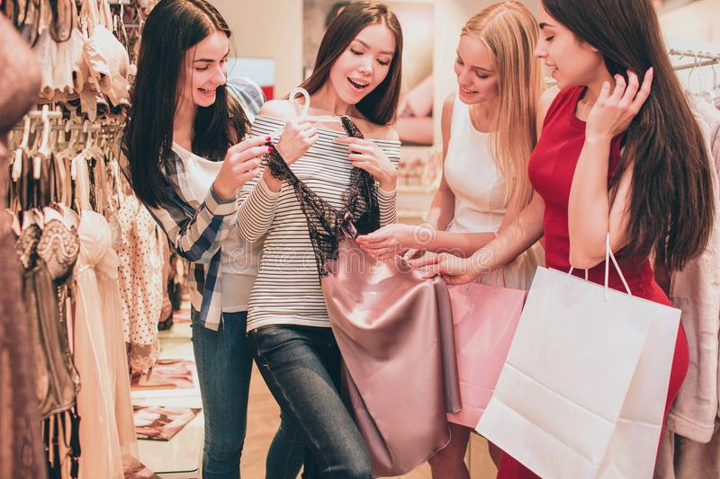 Asian girl is holding lace night shirt. It is very beautiful. Girls are looking at this shirt as well and touching it royalty free stock photos