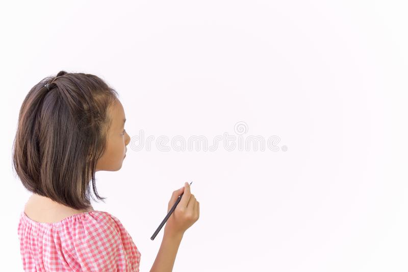 Asian girl holding pencil as mockup for you design in empty space isolated on white backgroud,closeup of cute child having an idea royalty free stock photography