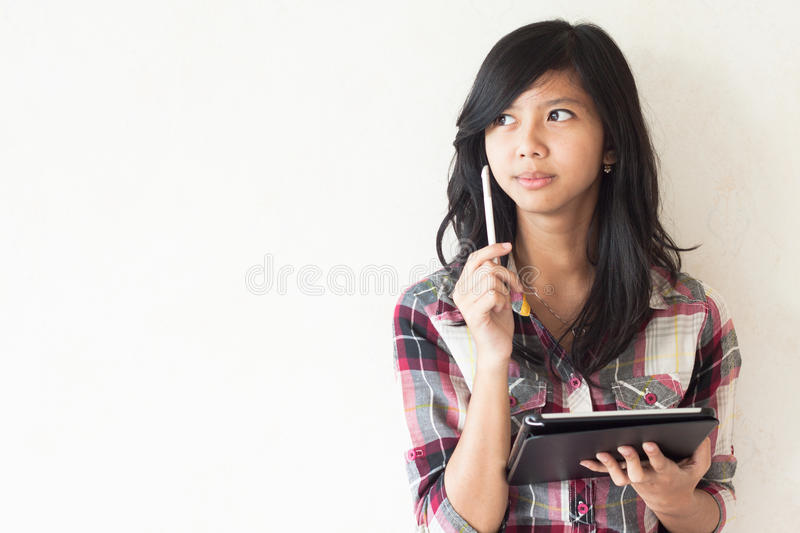 Asian Girl Holding A Tablet Pc And Thinking About Some Idea Stock Photo