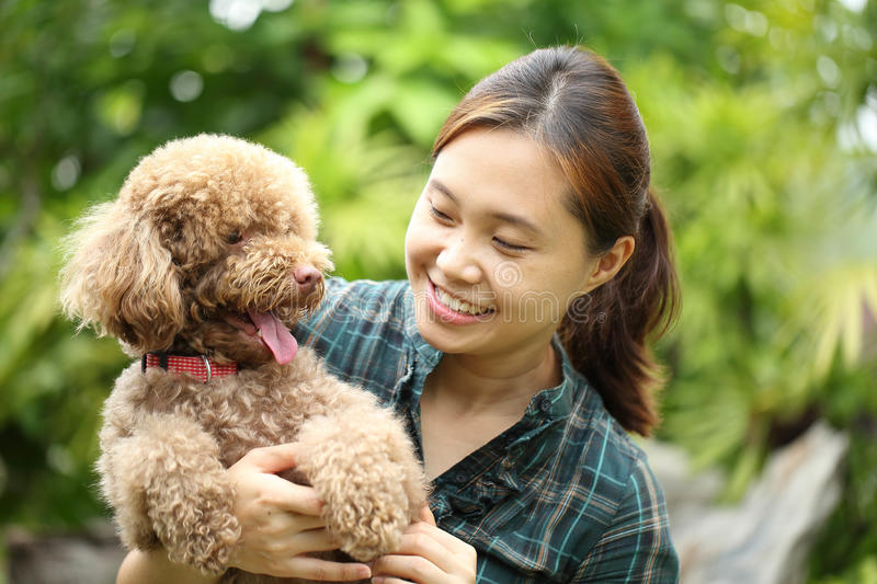 Asian girl hug with her poodle dog. In the garden royalty free stock images