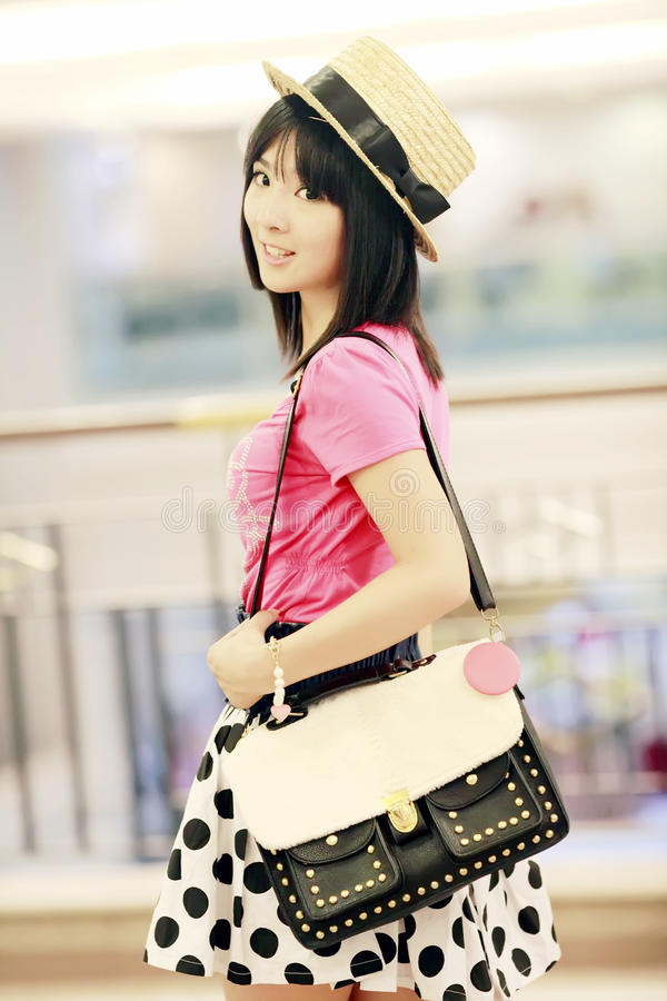 Asian girl indoor portrait. Charming Asian girl holding a handbag indoor portrait.(in a mall stock photography