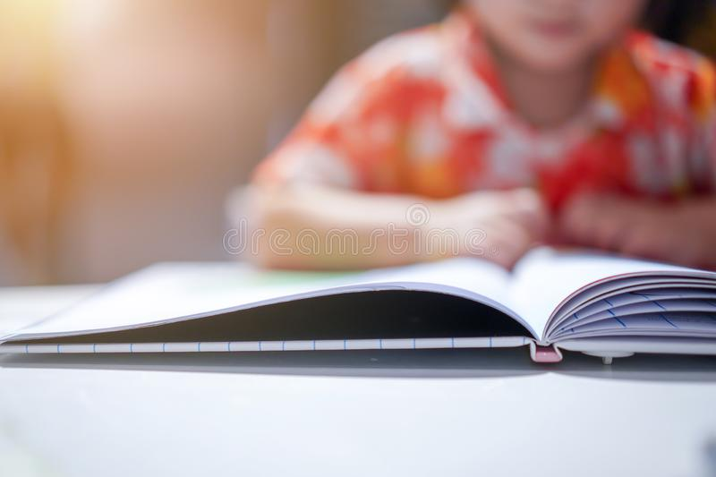 Asian girl kid concentrated read a book, close up at the book. With flare light royalty free stock photo