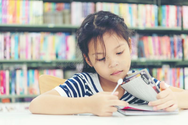 Asian girl in library reading something in a book and choosing a book in a library. stock image