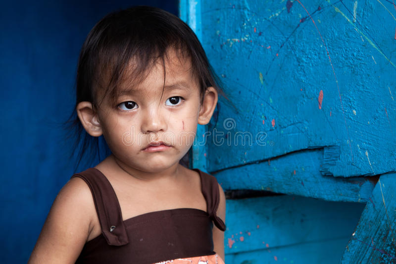 Asian girl living in poverty. Young Asian girl from poverty stricken area in Manila, Philippines royalty free stock photos