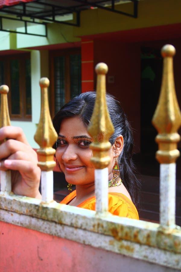 Asian Girl Looking through Metal Gate royalty free stock images