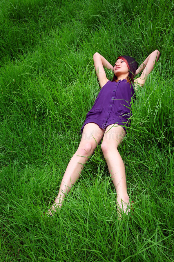 Asian girl lying on grass royalty free stock images