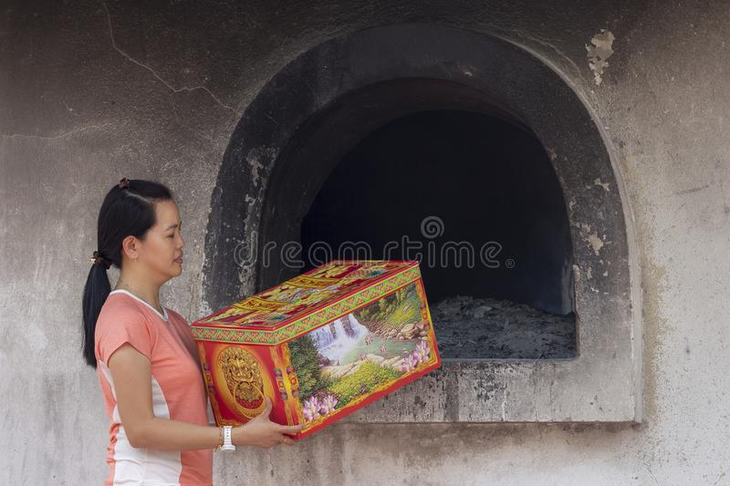 Asian girl offering Spirit money as a gift to the departed during Qing Ming festival royalty free stock image