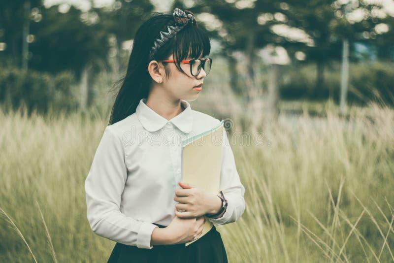 Asian girl outdoors holding folder stock photo