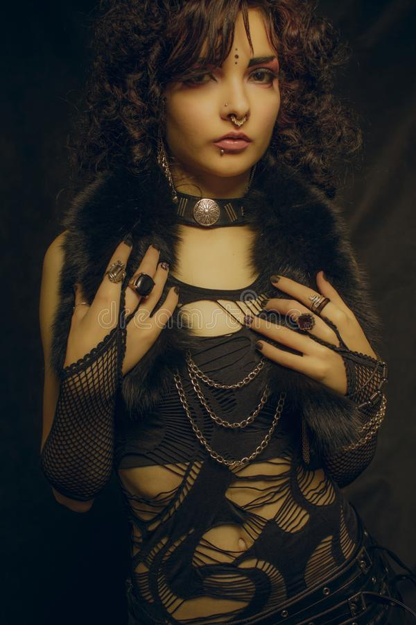 Lady with curly hairs. Asian girl with piercing posing over black background royalty free stock photography