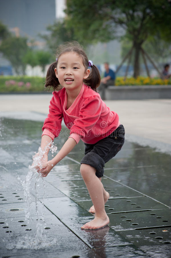Asian girl play Fountain royalty free stock image