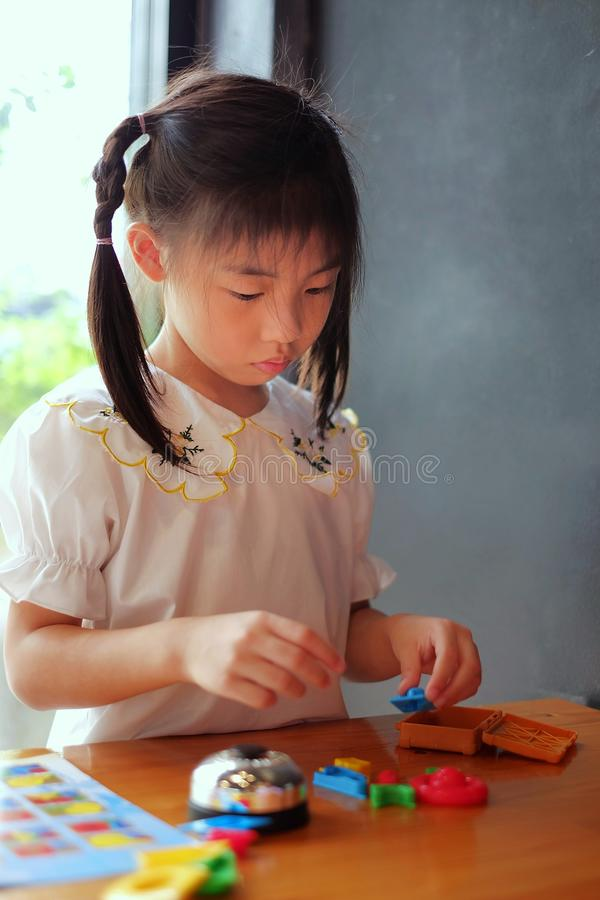 A Asian girl playing with colorful plastic toys from a board game on a wooden table. A cute Asian girl playing with colorful plastic toys from a board game on a stock images
