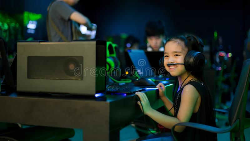 Asian girl playing computer games in internet cafe.  royalty free stock photo