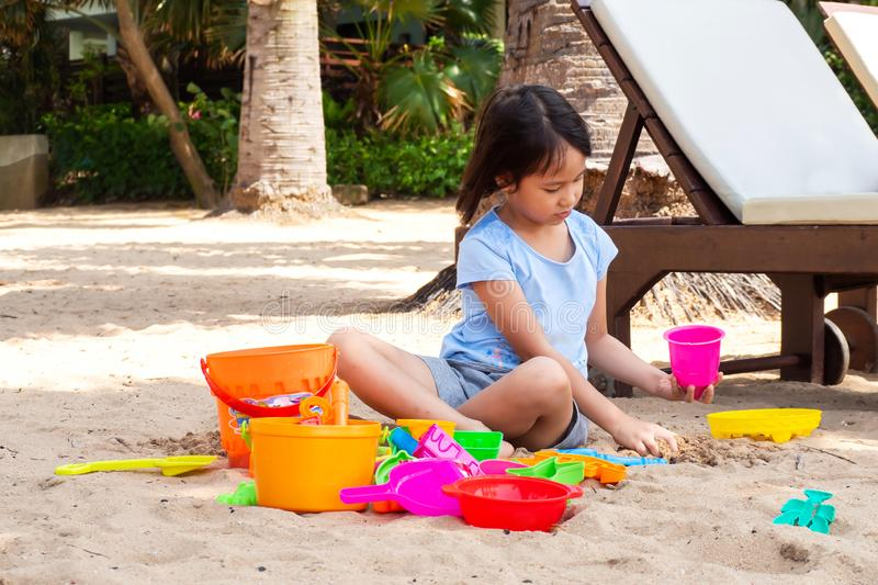 Asian girl playing sand with sand toys on beach royalty free stock image