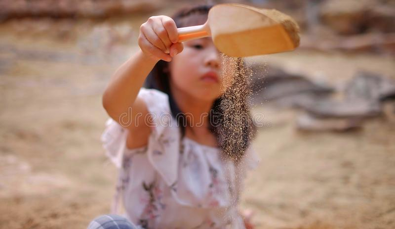 An Asian girl playing in a sandbox, sprinkling sand from a small shovel. A young Asian girl playing in a sandbox, sprinkling sand from a small shovel stock photography