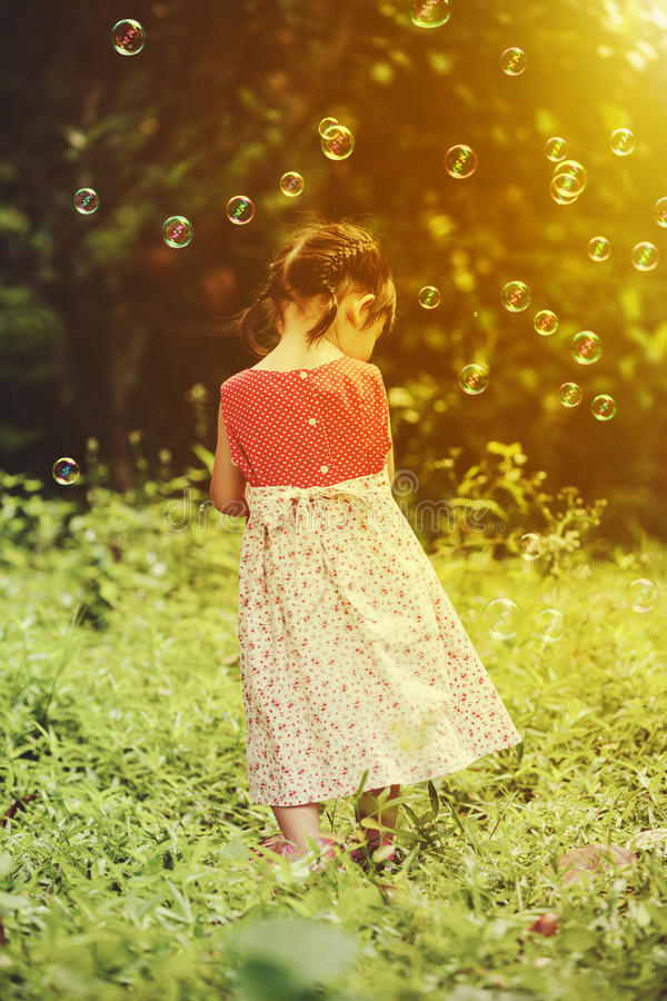 Asian girl playing with soap bubbles on nature background. Outdo stock images