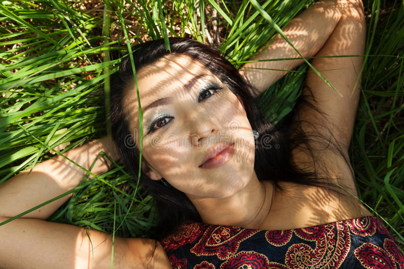 Asian girl portrait outdoors in the ferns shadows royalty free stock images