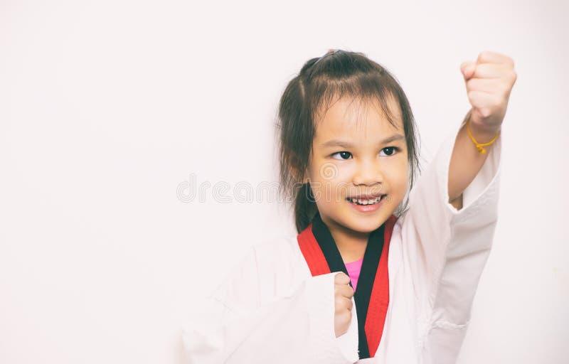 Asian girl is practicing Taekwondo on white. Background royalty free stock image