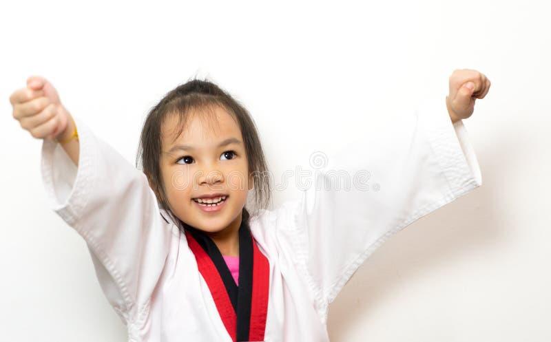 Asian girl is practicing Taekwondo on white. Background royalty free stock images