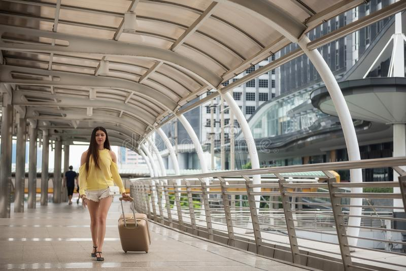 Asian girl pull luggage and shopping in city stock images
