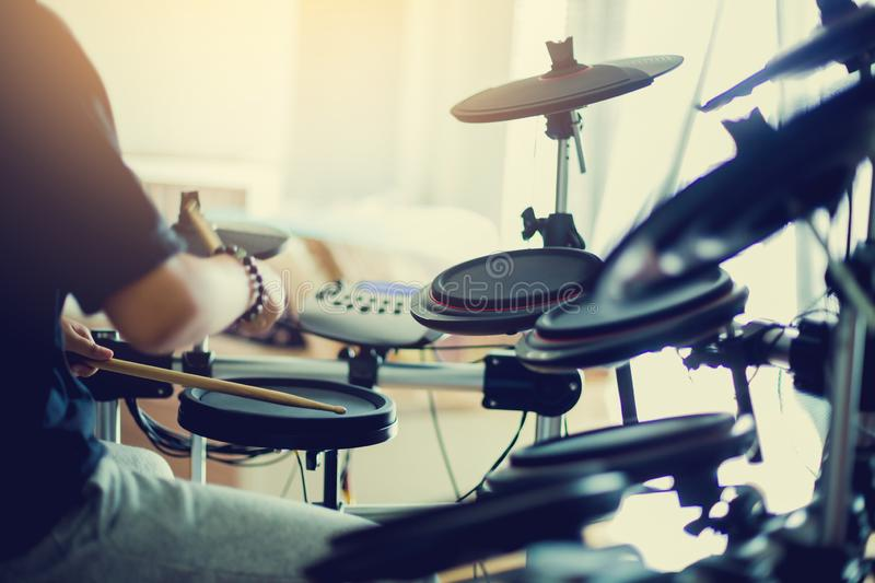 Asian girl put black tshirt and headphone learning and play electronic drum wooden drumsticks royalty free stock images