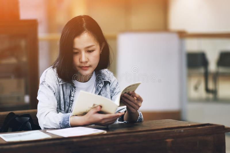 Asian girl reading books in coffee cafe. Female, people, young, beautiful, person, lifestyle, woman, happy, student, business, shop, relaxation, attractive royalty free stock images
