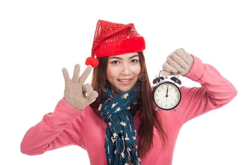 Asian girl with red christmas hat show OK and alarm clock. Isolated on white background stock photos