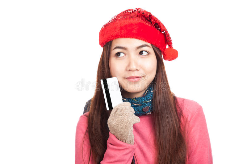 Asian girl with red christmas hat think and hold credit card. Asian girl with red christmas hat think and hold card isolated on white background royalty free stock photos