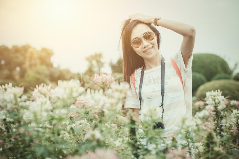 Asian girl relax enjoy holiday with photography flower hobby in the park stock photography