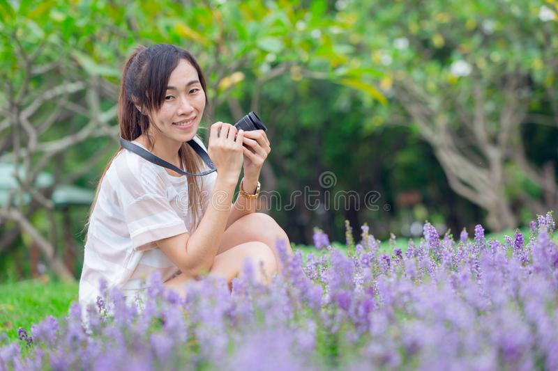 Asian girl relax enjoy holiday with photography flower hobby in the park royalty free stock image