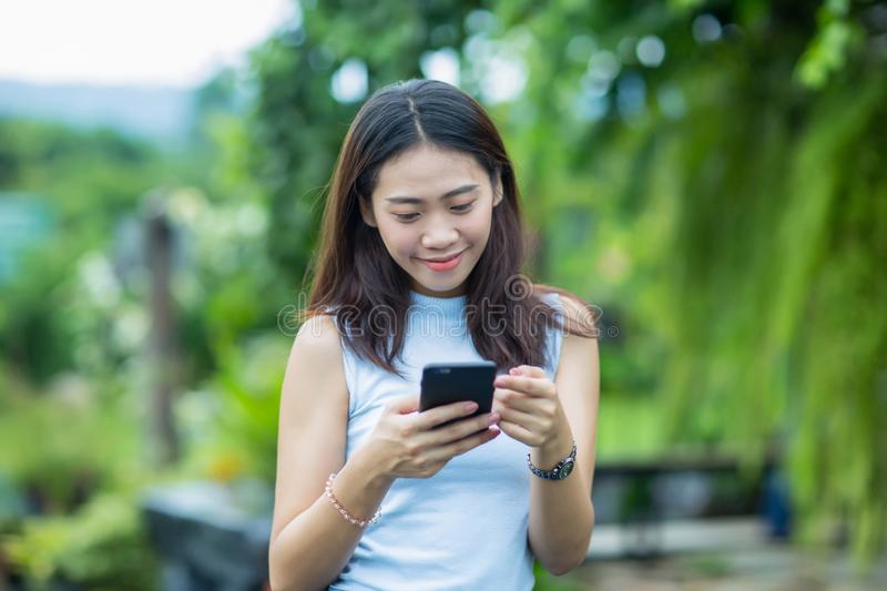 Asian girl relax in the garden with her cell phone stock photography