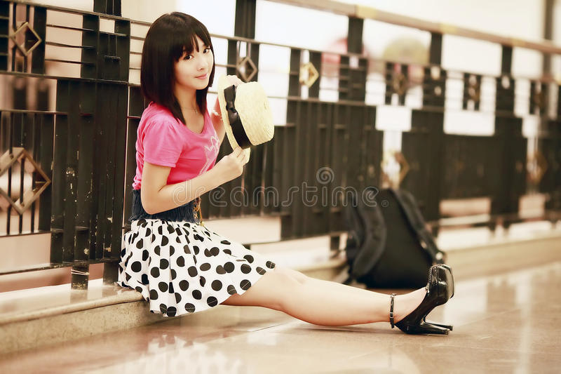 Asian girl relaxing indoor. Asian shopping girl holding a hat relaxing indoor mall stock image
