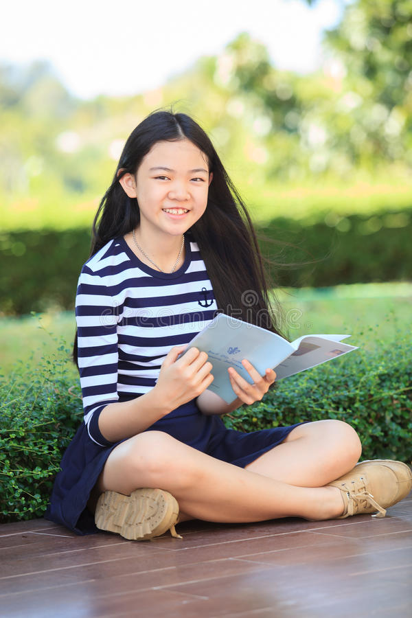 asian girl and school book in hand toothy smiling face with happiness emotion in green park stock images
