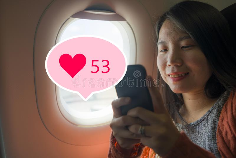 Asian girl sharing travel experience on social media . young happy beautiful Korean tourist woman in airplane cabin getting royalty free stock image
