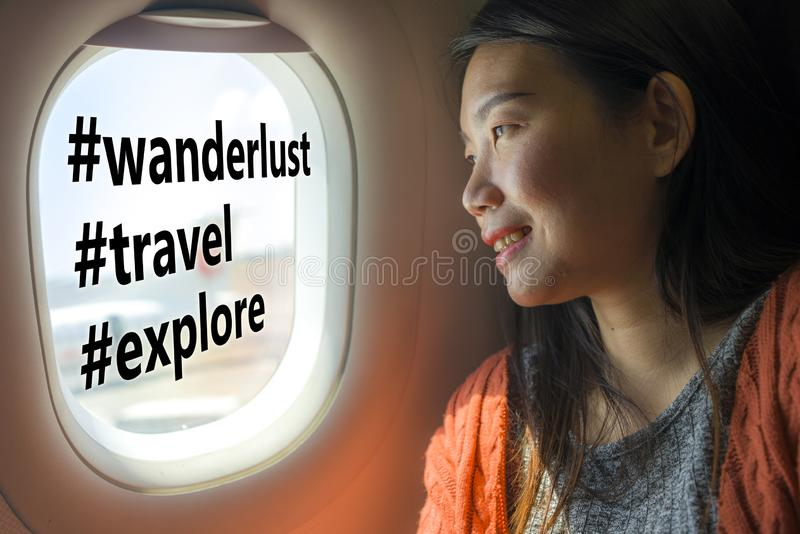 Asian girl sharing travel experience on social media . young happy and beautiful Korean tourist woman in airplane cabin thinking royalty free stock photo