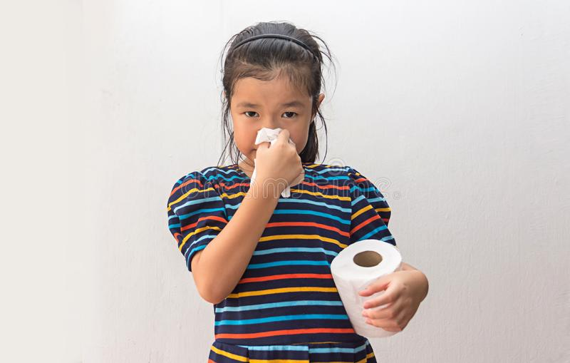 Asian girl sick with sneezing on nose and cold cough on tissue paper stock image