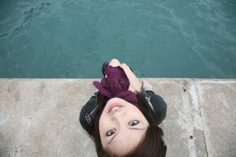 Asian girl sitting on edge royalty free stock image