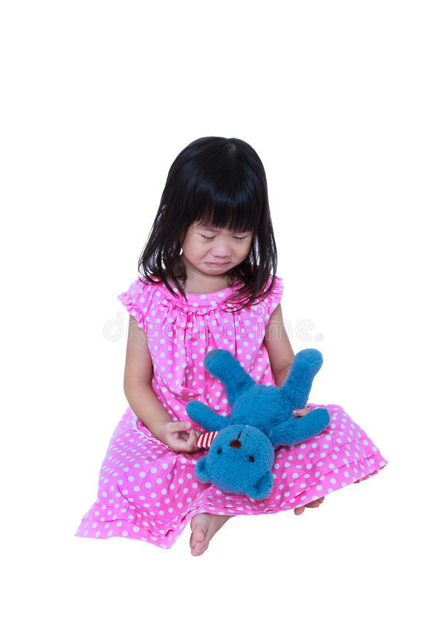 Asian girl sitting with toy bear, sadden and crying. Isolated on white stock photo