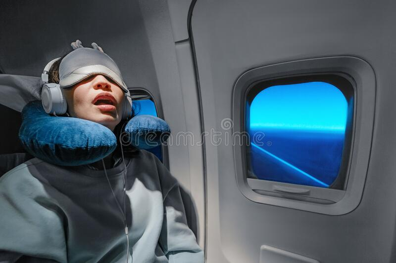 Girl sleeping in her seat on the plane near the window in a mask and with a pillow to sleep. The concept of travel with stock image