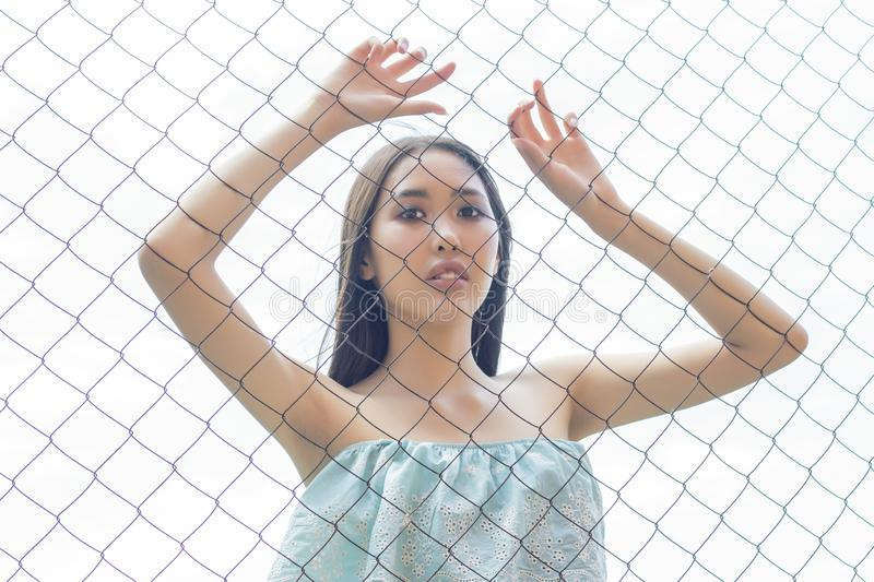 Asian girl standing behind  wire fence in a cage. holding her hands. concept stock image