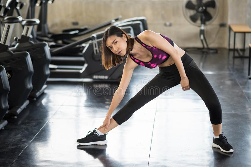 Asian girl stretching legs in gym royalty free stock photos